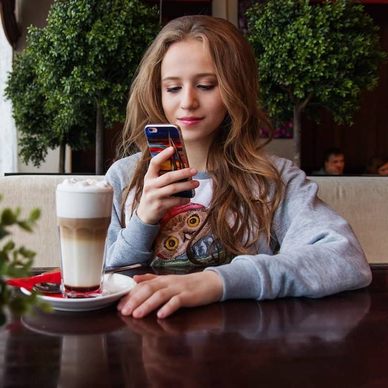 Fille lisant un menu numérique sur smartphone